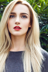 Close-up portrait of beautiful young woman with straight long blonde hair, green mysterious eyes and red sexy big lips posing next to the tree and looking to you through lens.