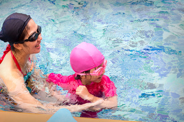 healthy family mother teaching little girl swimming pool