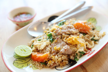 Pork fried rice with lime on wood background , Thai food