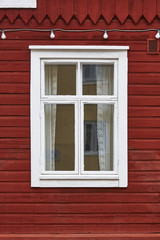 Traditional red wooden facade with white window. Vintage background