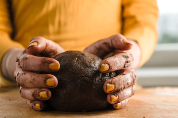 Ball of dough and cocoa in hands on a wooden board