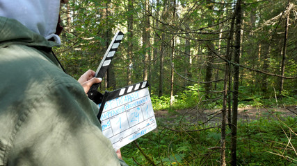 Movie clapper in forest. Clapperboard in forest. Film shooting in forest areas
