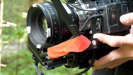 Man holding a camera filming a movie in the forest. Expensive camera for movie in the woods