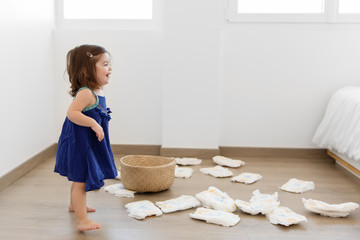 baby girl making mess with diapers on bedroom floor