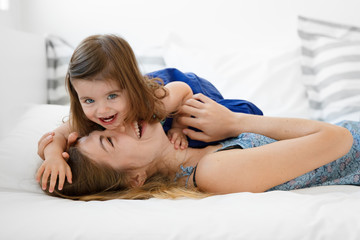 mother and baby girl snuggling on bed laughing together