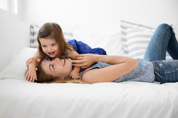mother and toddler girl snuggling on bed laughing together