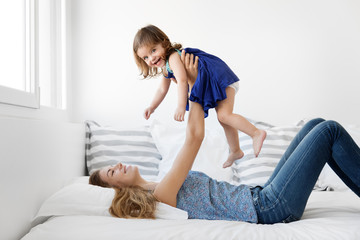 Mother lying on bed holding smiling toddler girl above her