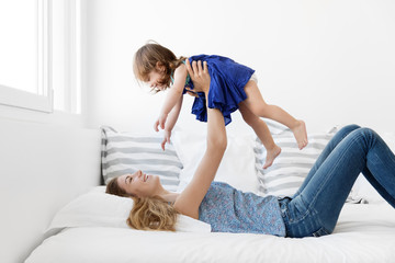 Mother lying on bed holding smiling baby girl above her