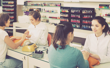 young nail technicians performing manicure procedure in beauty salon