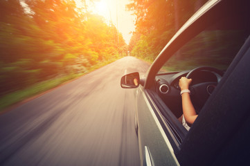 Young beautiful woman driving car - rear view Wall mural