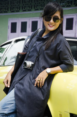 Asian thai woman travel and posing with retro yellow classic car at parking for show