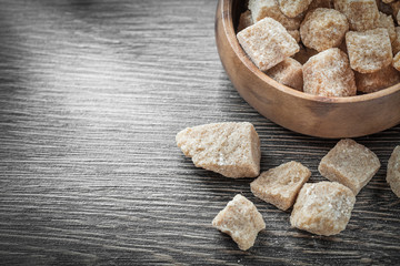 Brown sugar cubes in bowl on vintage wood board