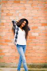 portrait of black african american woman with hat with brick wall background