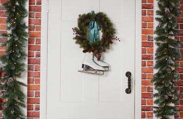 White skates hang with a spruce wreath. Christmas decoration of the front door of the house.