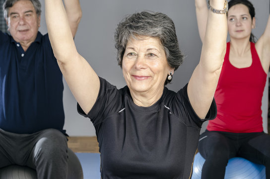 Diverse group of people a gym class sitting on Pilates ball doing ring Pilates exercise