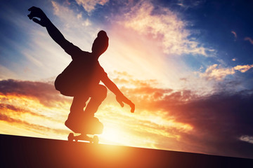 Man skateboarding at sunset.