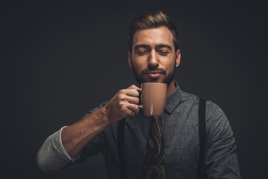 Handsome man smelling coffee
