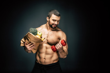 athletic man with healthy food and dumbbell