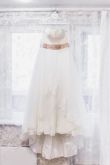 Beautiful white wedding dress hanging by window