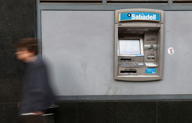 A woman walks past a cashpoint at the Sabadell bank branch in Barcelona