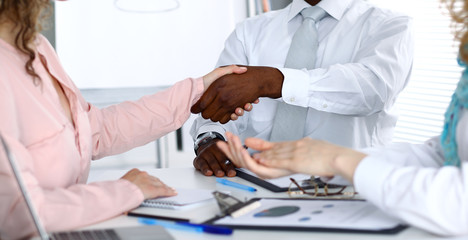 African american businessman shaking hands with female partner in office
