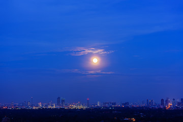 Scenery of full moon rising in blue hour , Bangkok , Thailand