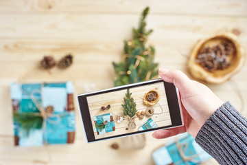 Hand taking photo of Christmas decorations on wooden table