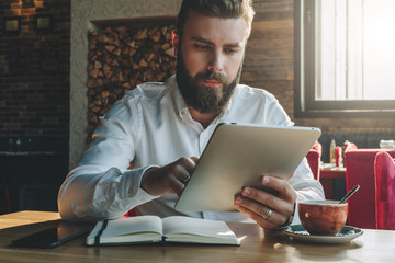 Young bearded businessman sits in office at table,uses tablet computer. On desk is notebook,smartphone, cup of tea.Man working, studying.Online education,marketing, training. E-learning, e-commerce.