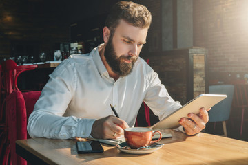 Young bearded businessman sits in cafe, home at table, uses tablet computer and writes in notebook. Man is working, student is studying. Online education, marketing, training. E-learning, e-commerce.