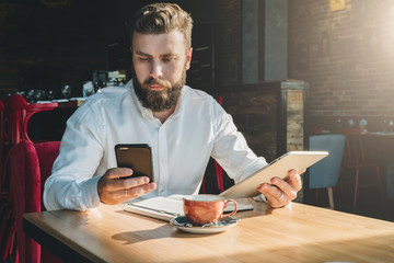 Young bearded businessman,dressed in white shirt, sits in cafe at table, holds digital tablet, uses smartphone.There is notebook on table,cup of coffee.Online education,marketing,training.E-learning.