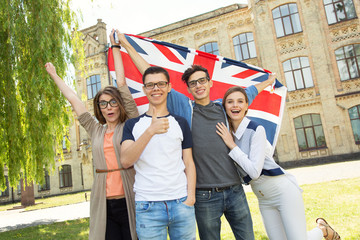 Group of students holding a flag of Great Britain on the university campus background.