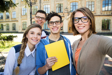 Cheerful selfie photo of a group of students on a university background. Four friends.