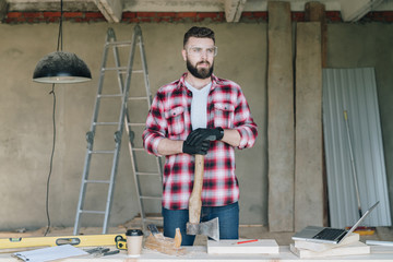 Young bearded businessman, builder, repairman, carpenter, architect, designer dressed in plaid shirt, goggles and gloves, stands in workshop and holds ax, hatchet in his hand. Handyman working.