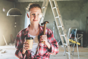 Front view. Portrait of happy young female construction worker, carpenter, repairman standing in workshop wearing safety glasses, holding hammer and cup of coffee in his hand.In background stepladder.