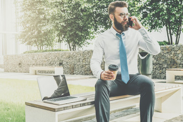 Young businessman in white shirt and tie is sitting outside on bench,drinking coffee and talking on his cell phone.Nearby is laptop.Man is working.Negotiations by phone. Business planning.E-marketing.