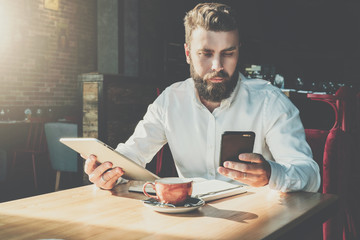 Young serious bearded businessman sits in cafe at table, holds digital tablet, uses smartphone.There is notebook on table,cup of coffee.Online education,marketing,training.E-learning.Instagram filter.