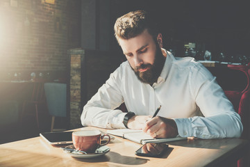 Young bearded businessman sits in cafe at table and writes in notebook.On table tablet computer, smartphone.Man is working, planning.Online education,marketing.E-learning, e-commerce.Instagram filter.