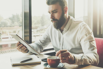 Young bearded businessman sits in cafe at table, uses digital tablet.On desk is notebook,cup of coffee.Man working,studying.Online education,marketing,training.E-learning,e-commerce. Instagram filter.