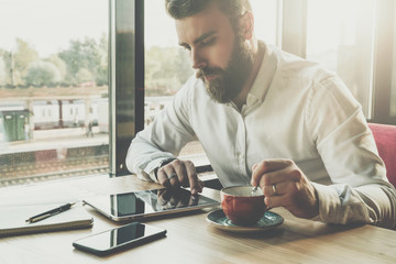 Young bearded businessman sits in office at table,uses tablet computer.On desk is notebook,smartphone.Man working,studying.Online education,marketing,training.E-learning, e-commerce. Instagram filter.