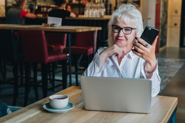 Businesswoman in glasses is sitting at table in front of laptop and holding smartphone.Education for adults. Freelancer works. Retired woman is chatting, blogging, checking email.Social media, network