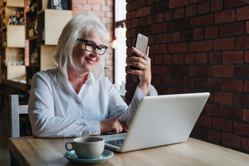 Smiling businesswoman is sitting at table in front of laptop and using smartphone. Education for adults. Pensioner freelancer works. Woman is chatting, blogging, checking email. Social media, network.