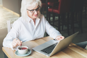 Smiling businesswoman in glasses sitting at table, working on laptop and drinking tea. Education for adults. Pensioner freelancer works. The woman is chatting, blogging, checking email. E-marketing.
