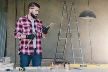 Bearded hipster man is carpenter, builder, designer stands in workshop,holds clipboard and hammer, reads instruction.On desk construction tools,in background stepladder.Repair, construction,carpentry.