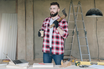 Young bearded businessman, builder, repairman, carpenter, architect, designer dressed in plaid shirt, goggles and gloves, stands in workshop, drinks coffee and holds ax, hatchet in his hand.