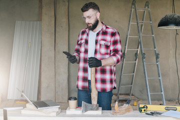 Young bearded businessman, builder, repairman, carpenter, architect, designer dressed in plaid shirt, goggles and gloves, stands in workshop, using smartphone and holds ax, hatchet in his hand.