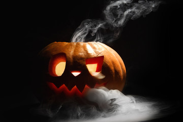 Halloween pumpkin lantern with dry leaves with burning candles