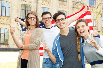 Group of students holding flag of USA on the university campus. Group four happy people having...