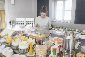 Woman taking cheese from breakfast buffet