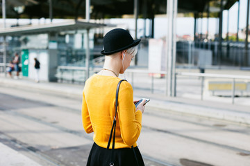 Chic woman using her smartphone waiting on the train station.