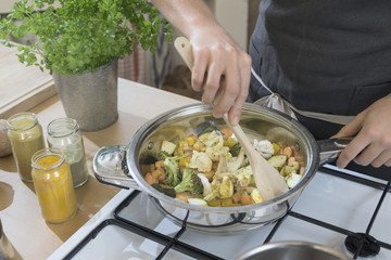 Woman stirring vegetables with spoon in pan